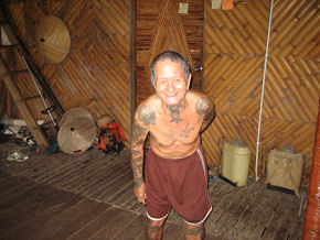 With former Bornean headhunter, known as Dr Unding, in traditional longhouse, Sarawak